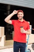 Fényképek kávé, hogy menjen a kezében és a rakomány mögött vidám szállítási férfi portréja
