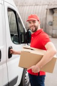 Fotografie smiling delivery man in uniform with cardboard box standing near white van in street