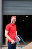Fényképek oldalnézetből a mosolygó kézbesítő karton doboz szállítás kocsi