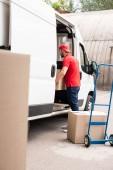 Fotografie young delivery man discharging cardboard boxes from van