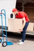mladí doručovatel vybíjení karton krabice z van