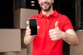 oříznuté záběr veselá doručovatel s smartphone ukazuje palec