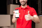 partial view of cheerful delivery man with smartphone with ebay logo on screen showing thumb up