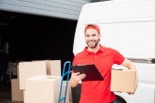 Fotografie portrait of young smiling delivery man with cardboard box and notepad