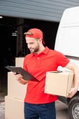 Photo portrait of young delivery man with cardboard box and notepad