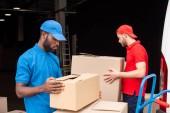 Fotografie boční pohled na multikulturní stěhováci v červené a modré uniformu s kartony