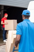 Fotografie multiethnic delivery men in red and blue uniform with cardboard boxes