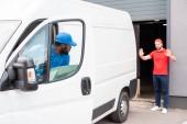Fotografie mnohonárodnostní dodání muži v uniformách parkování bílé van na ulici