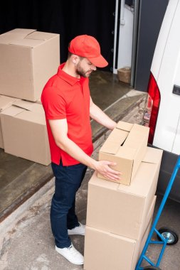 high angle view of young delivery man discharging cardboard boxes from van