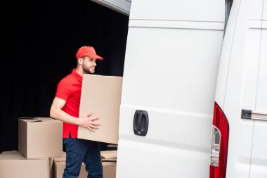 side view of young delivery man discharging cardboard boxes from van