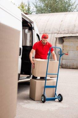 Young delivery man discharging cardboard boxes from van stock vector