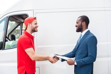 smiling delivery man and african american businessman shaking hands near van