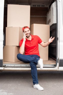smiling delivery man in red uniform talking on smartphone while resting in van with cardboard boxes