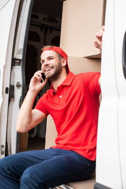 smiling delivery man in red uniform talking on smartphone while resting in van