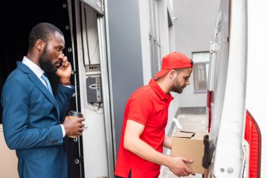 african american businessman with coffee to go controlling caucasian delivery man while talking on smartphone