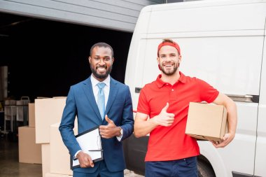 portrait of smiling multicultural client and delivery man showing thumbs up with cargo behind