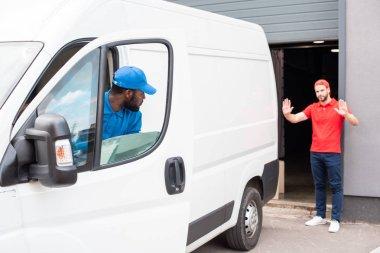 multiethnic delivery men in uniform parking white van on street