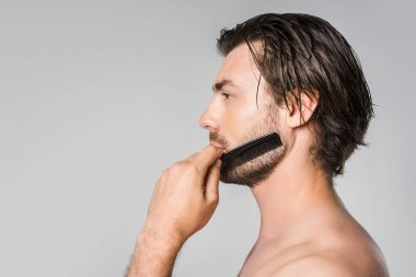 side view of man brushing beard with comb isolated on grey