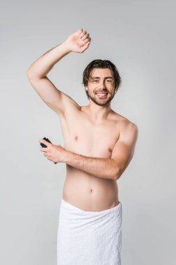 portrait of smiling man in white towel with male deodorant isolated on grey