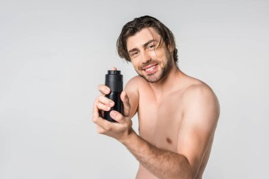 portrait of handsome man with male deodorant isolated on grey