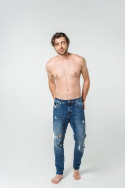 young shirtless man in jeans posing on grey backdrop