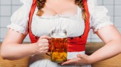 cropped image of oktoberfest waitress in traditional german dress holding mug of light beer near bar counter