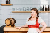 Fotografie attraktive Oktoberfest Kellnerin in Bayerischer Tracht Stand in der Nähe der Bartheke mit Bierfaß