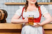 Fotografie oříznuté imageo oktoberfest barman v tradiční bavorské kroje hospodářství hrnek světlé pivo u baru