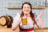 Oktoberfest-Barkeeper mit bekleideten Augen in bayerischer Tracht genießt den Geruch von leichtem Bier in der Nähe der Theke
