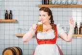 Photo smiling oktoberfest waitress in traditional bavarian dress drinking light beer near bar counter