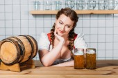 Photo smiling oktoberfest waitress in traditional german dress standing at bar counter with beer barrel and two mugs of light beer