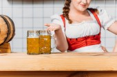Fotografie cropped image of oktoberfest waitress in traditional bavarian dress pointing at mugs of light beer on bar counter