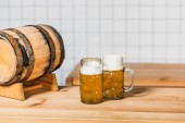 selective focus of mugs with light beer and barrel at bar counter