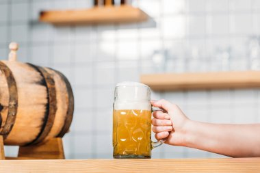 Cropped image of female bartender putting mug of light beer with foam on bar counter with beer barrel stock vector