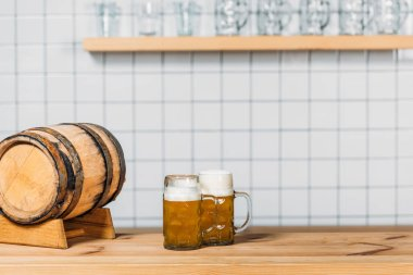 Selective focus of beer barrel and two mugs with light beer at bar counter stock vector