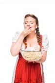 glücklich Wiesn-Kellnerin mit geschlossenen Augen in Bayerischer Tracht Essen Popcorn aus Schüssel isoliert auf weißem Hintergrund