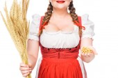 Fotografie cropped image of oktoberfest waitress in traditional german dress showing little pretzels and holding wheat isolated on white background