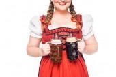 Teilansicht der Oktoberfestkellnerin in bayerischer Tracht mit Bechern mit hellem und dunklem Bier auf weißem Hintergrund