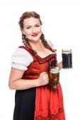 fröhliche Oktoberfestkellnerin in bayerischer Tracht mit Bechern mit hellem und dunklem Bier auf weißem Hintergrund