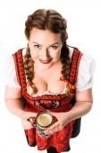 Vogelperspektive Blick lächelnder Oktoberfest Kellnerin in traditionellen bayerischen Kleid Holding Tasse Schwarzbier isoliert auf weißem Hintergrund