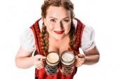 Hochblickaufnahme der Oktoberfestkellnerin in traditioneller bayerischer Tracht mit Bechern mit hellem und dunklem Bier isoliert auf weißem Hintergrund
