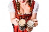 Zugeschnittenes Bild einer Oktoberfestkellnerin in bayerischer Tracht mit Krügen mit hellem und dunklem Bier auf weißem Hintergrund