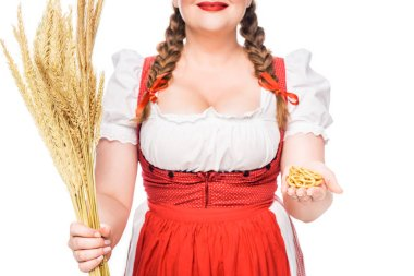 cropped image of oktoberfest waitress in traditional german dress showing little pretzels and holding wheat isolated on white background