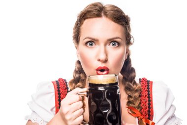 shocked oktoberfest waitress in traditional bavarian dress holding mug of dark beer isolated on white background