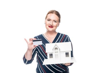 Happy female estate agent showing maquette of new house and credit card isolated on white background stock vector