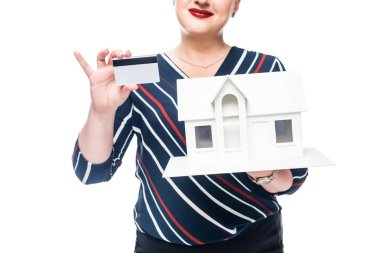 Cropped image of female realtor showing maquette of new house and credit card isolated on white background stock vector