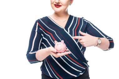 cropped image of businesswoman pointing at pink piggy bank isolated on white background