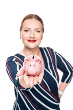 selective focus of businesswoman showing pink piggy bank isolated on white background