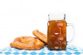 close up view of mug of beer and pretzels on table with table cloth on white background