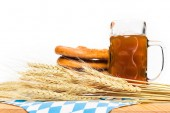 close up view of wheat ears, mug of beer and pretzels on table with table cloth on white background